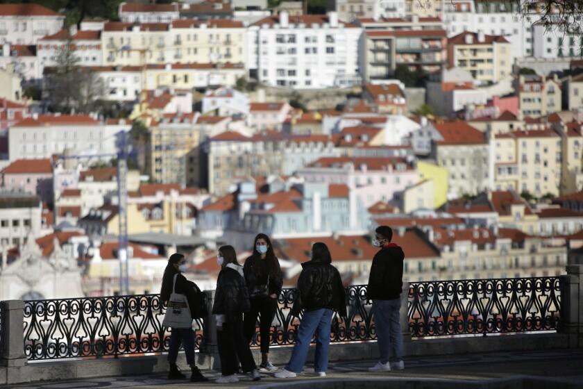 ARCHIVO - En esta foto de archivo del 11 de marzo de 2021, jóvenes con mascarillas conversan en un mirador sobre el centro histórico de Lisboa. En los próximos fines de semana estará prohibido entrar o salir de la zona metropolitana de Lisboa debido a un pico de contagios de COVID-19, informaron las autoridades el jueves 17 de junio de 2021. (AP Foto/Armando Franca)