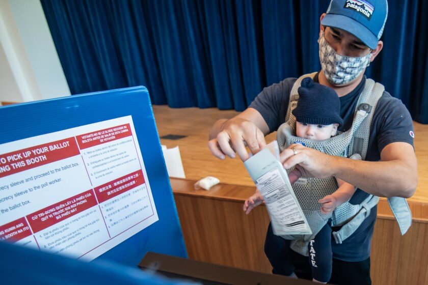 Ken Dugan wears a mask while voting at the San Marcos Civic Center