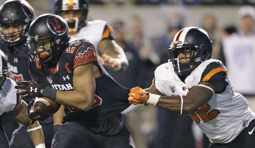Utah running back Devontae Booker (23) drags Oregon State linebacker Jonathan Willis, right, as he carries the ball in the second half during an NCAA college football game Saturday, Oct. 31, 2015, in Salt Lake City. Utah won 27-12. (AP Photo/Rick Bowmer)