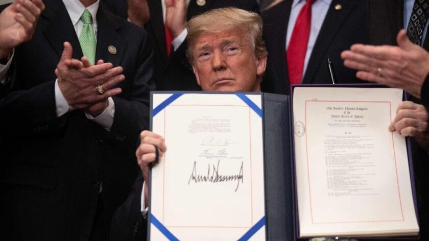 President Trump shows off his signature on the Economic Growth, Regulatory Relief and Consumer Protection Act at the White House on May 24.