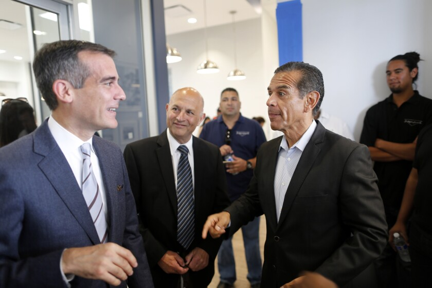 Mayor Eric Garcetti and former mayor Antonio Villaraigosa meet at the opening of the Community Coalition's newly renovated South L.A. headquarters building on Vermont Ave. last month.