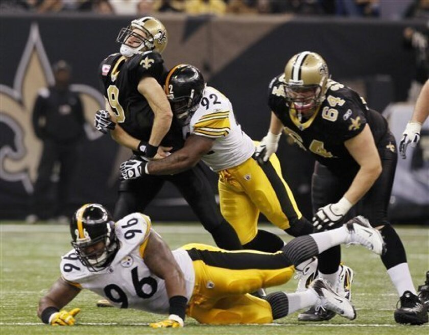 New Orleans Saints quarterback Drew Brees (9) is hit by Pittsburgh Steelers linebacker James Harrison (92) after releasing a pass during the first half of an NFL football game at the Louisiana Superdome in New Orleans, Sunday, Oct. 31, 2010. Also in on the play are Steelers defensive end Ziggy Hood (96) and Saints offensive tackle Zach Strief (64). (AP Photo/Patrick Semansky)