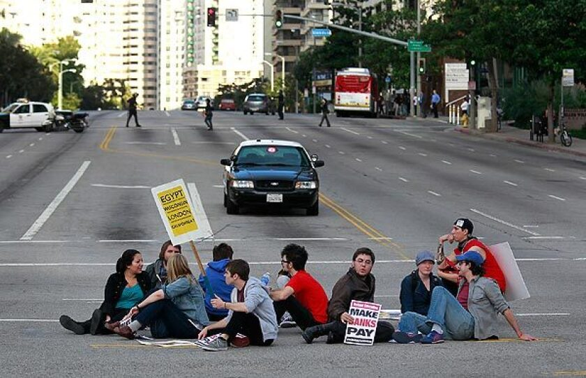 UCLA students sit in the middle of the intersection of Wilshire and Westwood boulevards, where traffic was shut down for hours Wednesday. Eleven people were arrested on suspicion of failing to disperse.