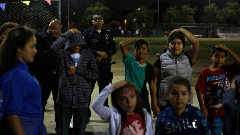 LAPD Officer Roger Medina watches as kids play during the Summer Night Lights program at the Costello Recreation Center in Boyle Heights.