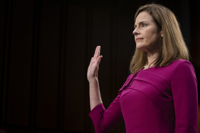 Amy Coney Barrett holds up her right hand to be sworn in before Monday's hearing.