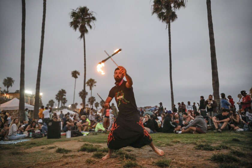 Nate Endless twirls a fire baton in Ocean Beach on July 29.