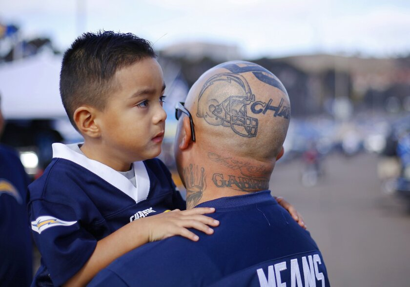 SAN DIEGO, CA -DEC. 20, 2015 - Chargers season ticket holder Douglas Vasquez holds his son Gabriel, 4, in the parking lot at Qualcomm Stadium before the Dolphins game.   (K.C. Alfred/ San Diego Union-Tribune)