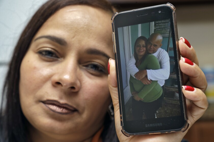 In this Wednesday, Feb. 26, 2020 photo, Yarelis Gutierrez Barrios holds up a cell phone photo at her home in Tampa, Fla., of herself with her partner Roylan Hernandez Diaz, a Cuban asylum seeker who hanged himself in a Louisiana prison. An Associated Press investigation into Hernandez's death last October found neglect and apparent violations of government policies by jailers under U.S. Immigration and Customs Enforcement. (AP Photo/Chris O'Meara)