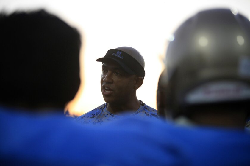 Brandon Hawkins talks to his players before his first game as head coach at San Ysidro. Hawkins took over after Terry Tucker stepped down last weekend.