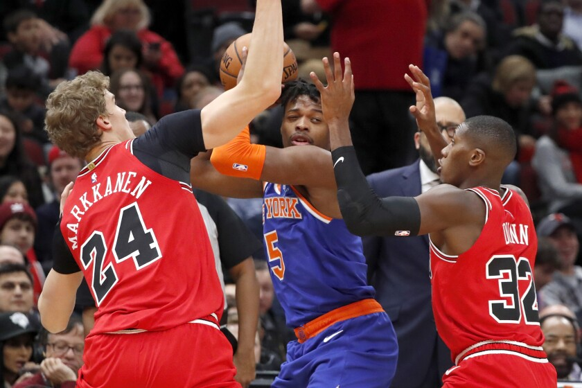 Chicago Bulls' Lauri Markkanen (24) and Kris Dunn (32) pressure New York Knicks' Dennis Smith Jr. during the first half of an NBA basketball game Tuesday, Nov. 12, 2019, in Chicago. (AP Photo/Charles Rex Arbogast)