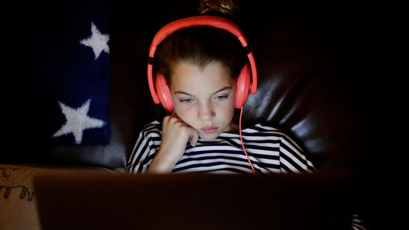 A child, 10, watches a video during her 15 minutes of computer time at her home in San Jose, Calif. on Dec. 14.
