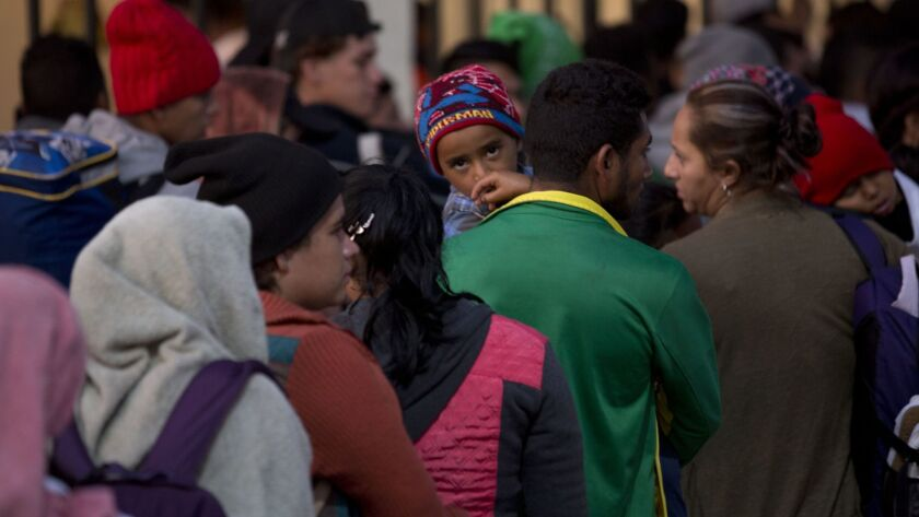 Migrants of Honduras and El Salvador stand in line waiting to enter bridge over the Suchiate River o