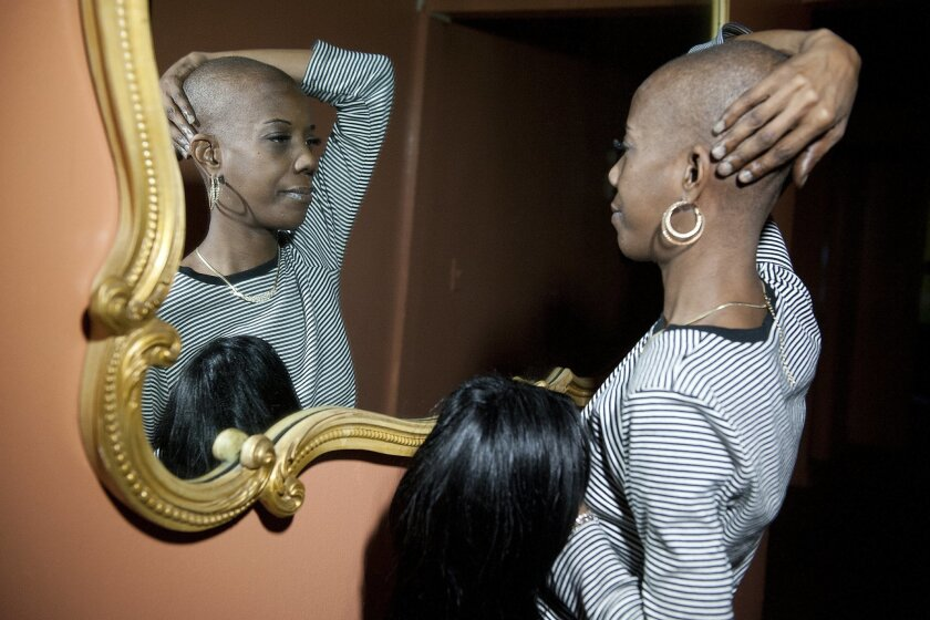 In this Nov. 26, 2014 photo, Marcy Borders shows her shaved head, the result of in her chemotherapy treatment for stomach cancer, at her home in Bayonne, N.J. Borders, a survivor of the September 11, 2001 attacks on New York who was featured in one of the most iconic photographs of the day, died Monday, Aug. 24, 2015 after a battle with stomach cancer, her daughter said Wednesday. (Reena Rose Sibayan/The Jersey Journal via AP) MANDATORY CREDIT
