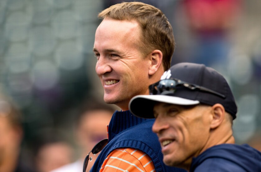 Peyton Manning shares a laugh with Yankees Manager Joe Girardi during batting practice before a game against the Colorado Rockies at Coors Field earlier this month.