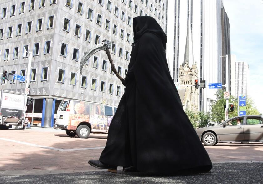 """En esta imagen del 10 de octubre de 2016 """"La Parca"""" está al acecho de peatones distraídos en Pittsburgh, Pennsylvania. La Sociedad del Centro de Pittsburgh y otros grupos intentan """"asustar"""" a los peatones para que dejen de utilizar sus teléfonos celulares mientras caminan, con actores disfrazados de Parcas y zombies, pidiéndoles que alejen la vista de sus smartphones mientras caminan por el centro. (Darrell Sapp/Pittsburgh Post-Gazette via AP)"""