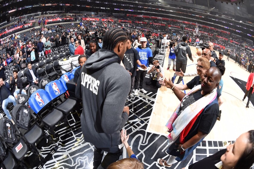 cClippers star Kawhi Leonard heads to the court with his former teachers lined up for high-fives.