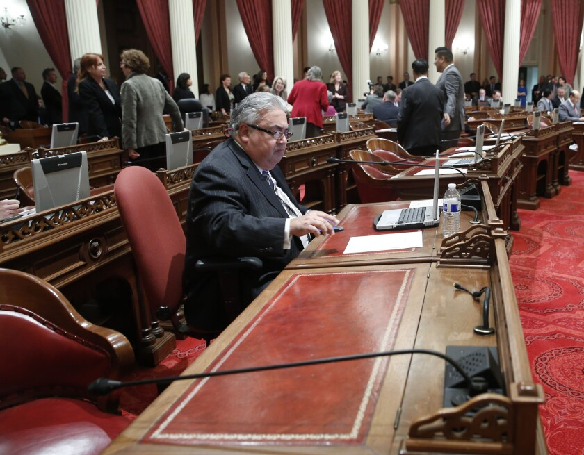 State Sen. Ronald S. Calderon (D-Montebello) works at his desk during a Senate session earlier this month. He was reassigned to the corner desk pending the outcome of a federal corruption investigation.