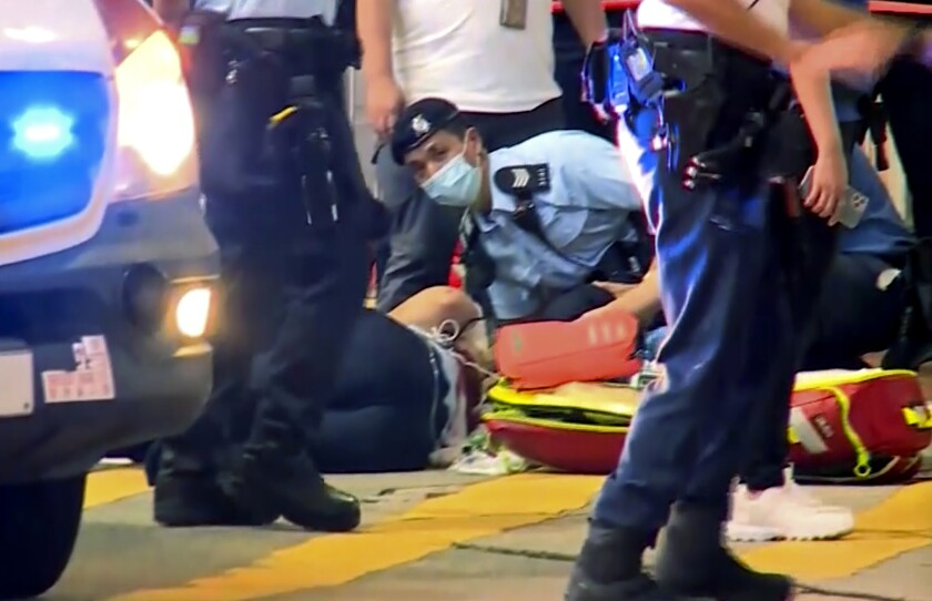 In this image made from video provided by TVB, a police officer on the ground receives medical treatment after being stabbed by a man on a street in Causeway Bay of Hong Kong, Thursday, July 1, 2021. The assailant, who authorities say was acting on his own, later knifed himself and was certified dead at the hospital. The attack came on the 24th anniversary of the handover of Hong Kong to China, on a day when police had for a second year in a row banned a yearly pro-democracy march as authorities cracked down on dissent. (TVB via AP Video)