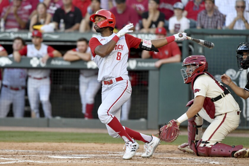 FILE - North Carolina State's Jose Torres (8) watches the ball after connecting for a home run against Arkansas in the ninth inning during an NCAA college baseball super regional game in Fayetteville, Ark., in this Sunday, June 13, 2021, file photo. Home runs — lots and lots of them — have defined the NCAA baseball tournament so far. A total of 381 have been hit in 123 games, the highest total through super regionals since at least 2005.(AP Photo/Michael Woods, File)