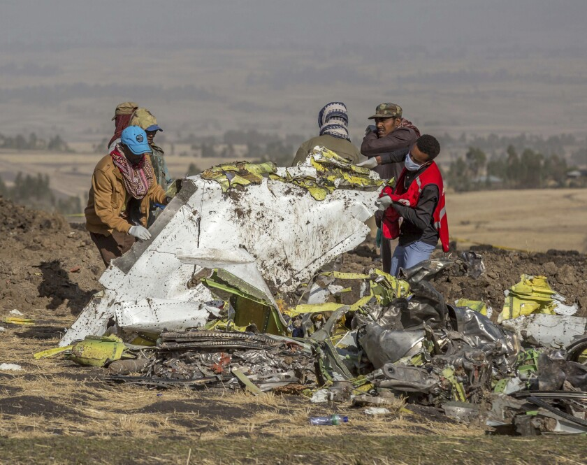 FILE - In this March 11, 2019, file photo, rescuers work at the scene of an Ethiopian Airlines flight crash outside of Addis Ababa, Ethiopia. Ethiopian Airlines' former chief engineer Yonas Yeshanew, who is seeking asylum in the U.S., says in a whistleblower complaint filed with regulators that the carrier went into maintenance records on a Boeing 737 Max jet after it crashed this year, a breach he contends was part of a pattern of corruption that included routinely signing off on shoddy repairs. (AP Photo/Mulugeta Ayene, File)