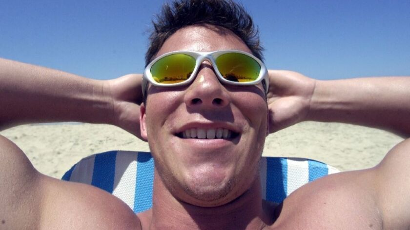 In a file photograph, a college student at Mission Beach blithely soaks up the rays that years later cause skin cancer.