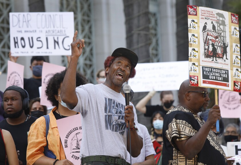 A man speaks into a microphone while next to people holding signs