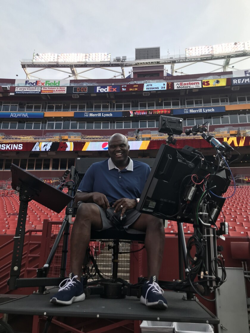 ESPN analyst Booger McFarland poses in the new elevated chair at FedEx Field in Washington.