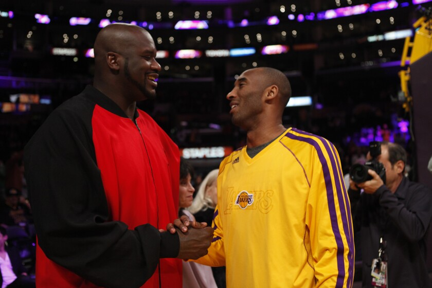 Former Laker Shaquille O'Neal is greeted by Kobe Bryant before a game at Staples Center on Feb. 12, 2013.