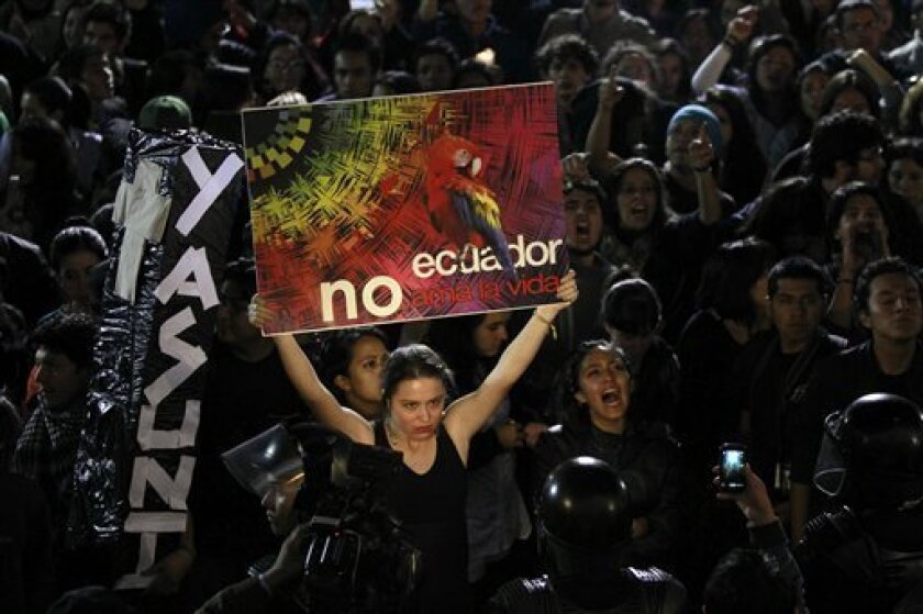 """A demonstrator holds a sign that reads in Spanish """"Ecuador doesn't love life"""" during a protest outside the government palace in Quito, Ecuador, Thursday, Aug. 15, 2013. Ecuador's President Rafael Correa said in a televised speech that he has abandoned a unique and ambitious plan to persuade rich co"""