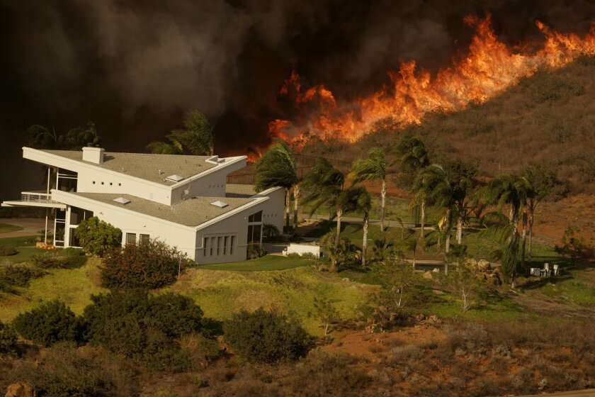 A line of fire approaches a home south of Highland Valley Road, east of Lake Ramona in 2007.