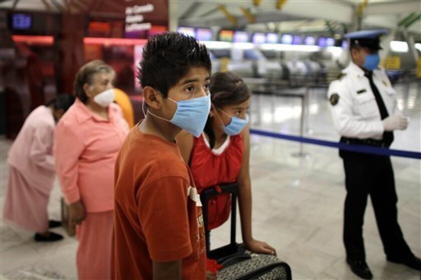 Passengers, wearing masks as a precaution against swine flu, prepare to depart from the Mexico City's International Airport in Mexico City, Tuesday, May 5, 2009. Mexican officials lowered their flu alert level in the capital on Monday, and plan to allow cafes, museums and libraries to reopen this week, while world health officials weighed raising their pandemic alert to the highest level. (AP Photo/Alexandre Meneghini)