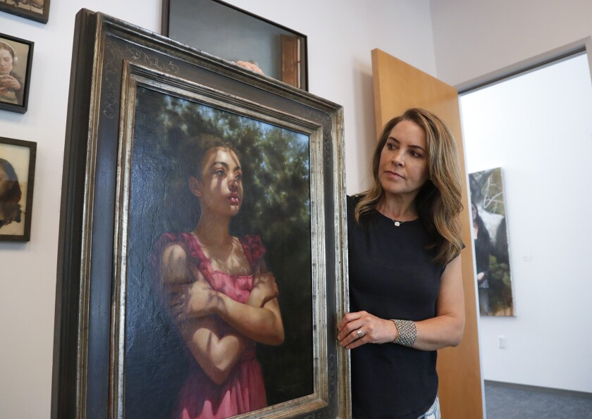 """Laguna College of Art and Design graduate Jody Gerber poses with her painting, """"Illusion."""""""