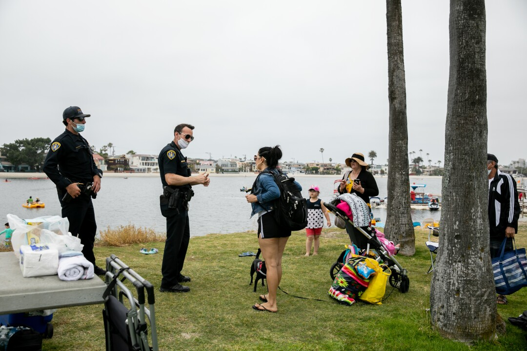 Two San Diego Police Department officers ask a family to move along, telling them they can't be seated on the bayfront at Mission Bay on Memorial Day.