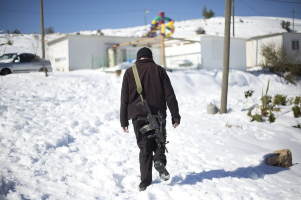 An armed Jewish settler walks in the West Bank Jewish outpost of Givat Asaf, north of the Palestinian city of Ramallah. A blustery storm, dubbed Alexa, has brought gusty winds, torrential rains and heavy snowfall to parts of the Middle East.