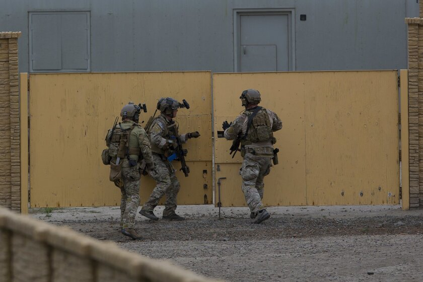 Army Special Forces personnel conduct a building-to-building search for civilian evacuees at a simulated United States Agency for International Development compound. The exercise, in June, was part of the Angel Thunder training at Camp Pendleton.
