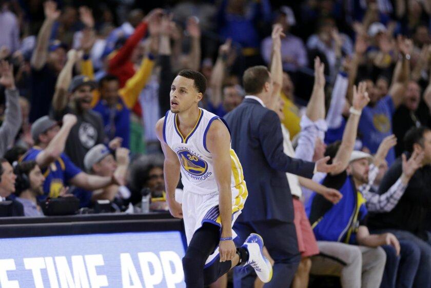 The crowd reacts as Golden State Warriors' Stephen Curry, center, makes a three-point basket against the Atlanta Hawks during the first half of an NBA basketball game Wednesday, March 18, 2015, in Oakland, Calif. (AP Photo/Marcio Jose Sanchez)