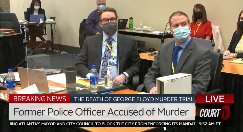 Attorney Eric Nelson and Minneapolis police officer Derek Chauvin sit at a desk, as seen on Court TV.