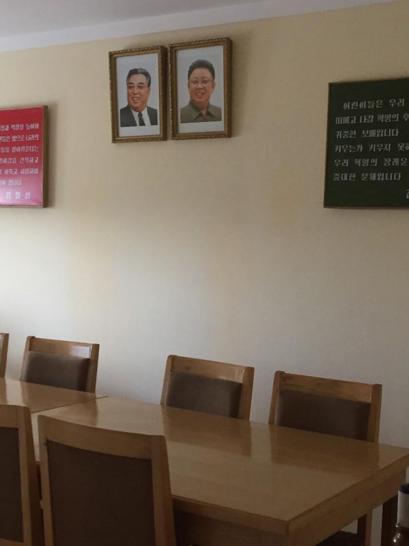Portraits of Kim Il Sung and Kim Jong Il hang on the wall at the Changchon