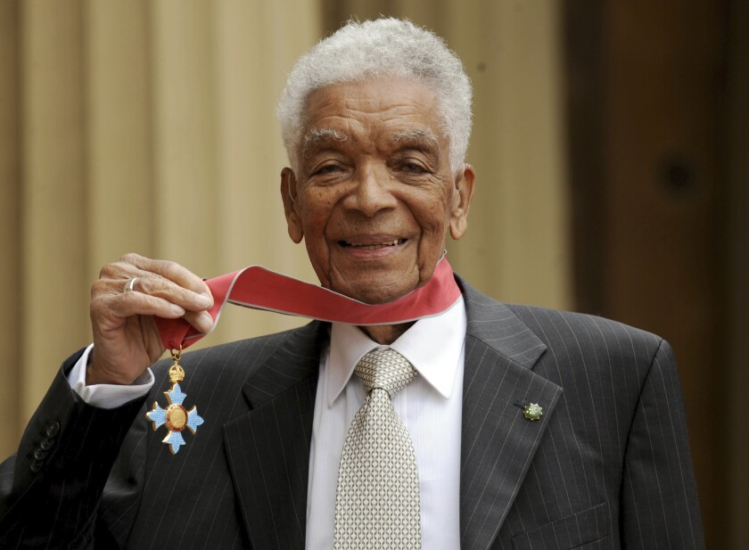 Earl Cameron poses for the media outside Buckingham Palace after being presented his CBE by Prince Charles, in London.