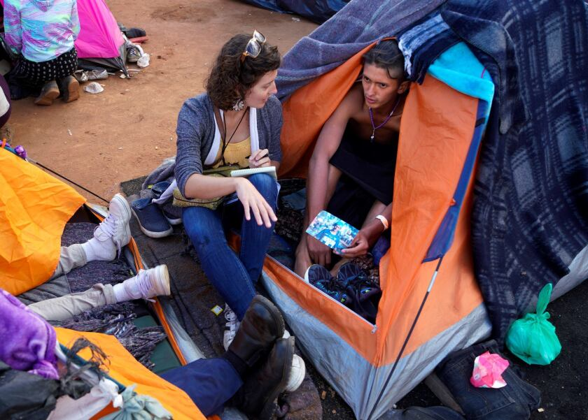 At the border, Kate Morrissey speaks with a person in the Central American migrant caravan.