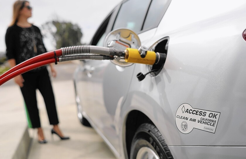 Honda employee Angie Nucci demonstrates how to fill a Honda Civic with natural gas at a CNG station in Torrance. The Civic is the only CNG sedan currently available in the U.S.