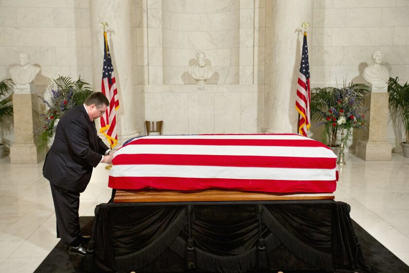 The flag covering the casket of late Supreme Court Justice Antonin Scalia is adjusted by funeral home staff before the doors opened to the public in the Great Hall of the Supreme Court in Washington, Friday, Feb. 19, 2016, where the late Justice lies in repose. (AP Photo/Jacquelyn Martin, Pool)
