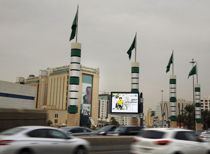 Vehicles pass in front of an illuminated advertisement for Saudi Aramco in Riyadh, Saudi Arabia.