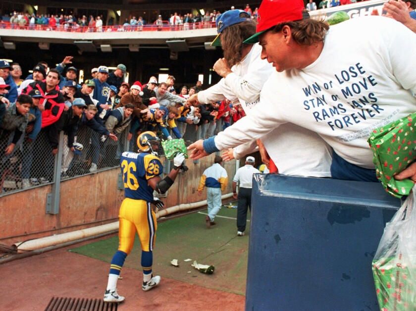 A Los Angeles Rams fan, wearing his sentiments on his shirt, hands safety Anthony Newman a gift after a game against the Redskins on Dec. 24, 1994 in Anaheim, Calif.