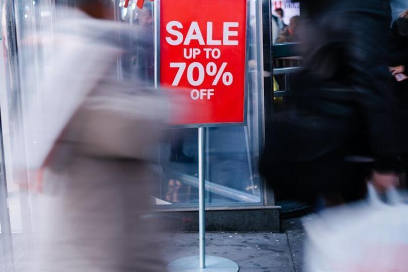 Personas cargan bolsas con sus compras afuera de un centro comercial. EFE/Archivo