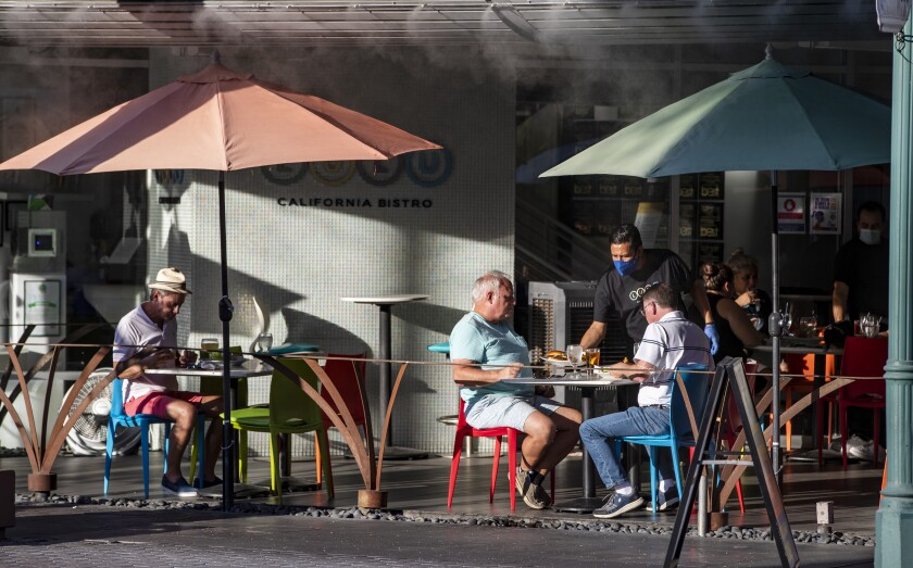 A waiter wearing a mask serves diners outside at Lulu's California Bistro in Palm Springs in July.