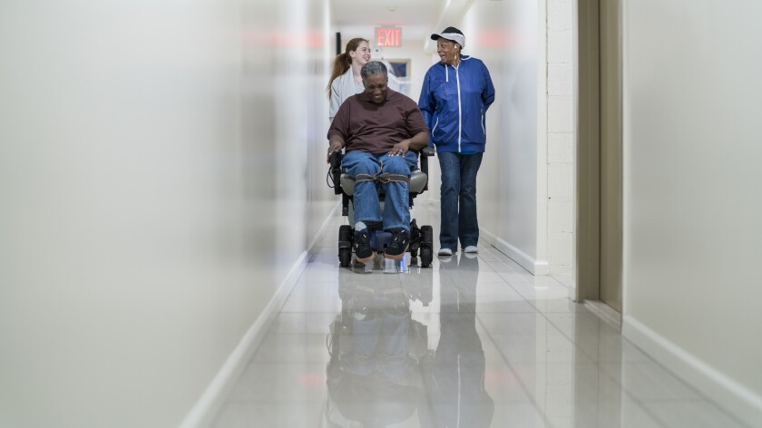 A Black man in wheelchair, accompanied with Black woman and White teenager girl, in the corridor of a nursing home.