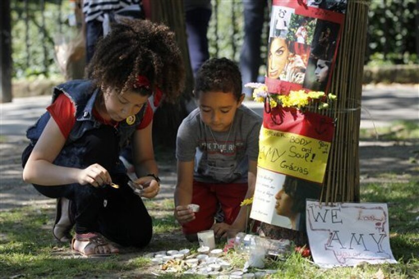 Young fans of British singer songwriter Amy Winehouse light candles for her outside her house in London on the first anniversary of her death, Monday, July 23, 2012. (AP Photo/Sang Tan)