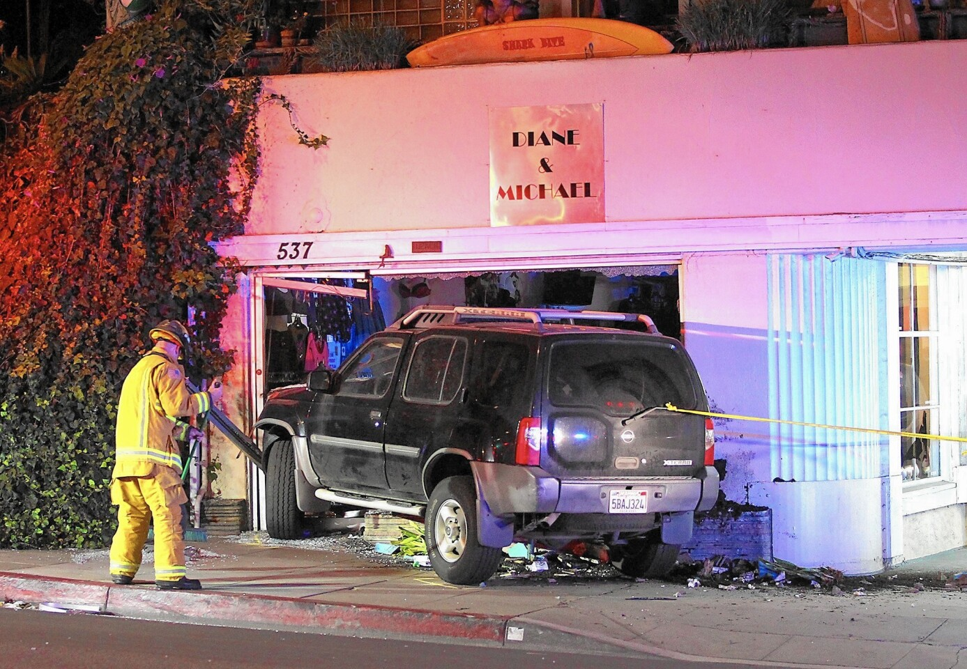 A Laguna Beach firefighter sweeps up debris where a Nissan X-Terra crashed through the front door and window display at the Diane and Michael Gallery at 537 S. Coast Hwy. just after 10 p.m. Friday.