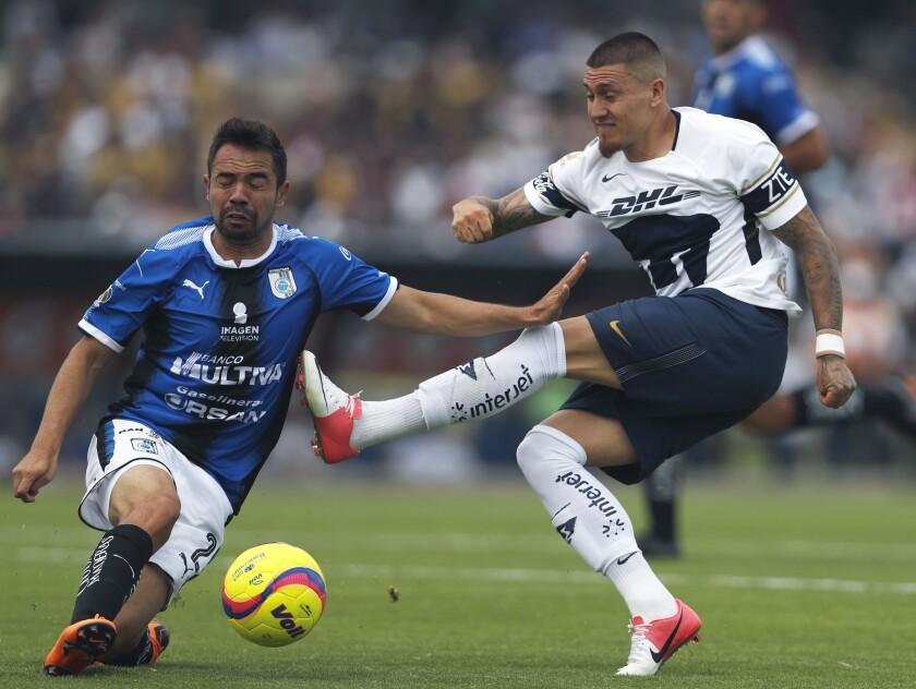 Queretaro's Josecarlos Van Rankin, left, blocks Pumas' Nicolas Castillo during a Mexican soccer league match in Mexico City, Sunday, April 29, 2018. Pumas and Queretaro tied 1-1.